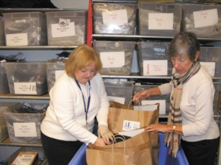 """League members Marilyn Steele, left, and Lynn Farrell, prepare bags of new clothing for children. Steele is the liaison between """"Operation School Bell,"""" and Fulton and DeKalb Public Schools' social workers, who identify youngsters in need."""