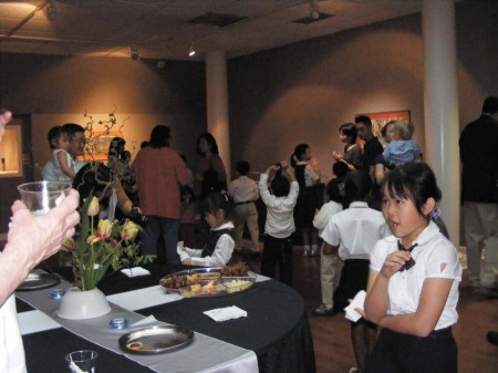 A student from the school mingles with art enthusiasts. The exhibition runs through Aug. 25.
