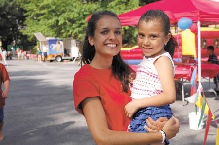 Lauren Evans, church youth director, gives Felisa Resindez, 6, a welcoming hug.