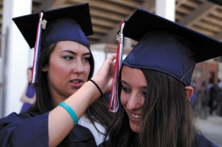 Emma Fincher, left, and Susan Bloom make some last-minute adjustments to their graduation attire.