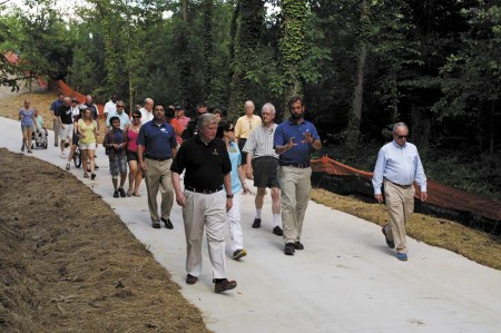 Brent Walker, Dunwoody Parks and Recreation Manager, center, leads city officials, council members and other members of the community in walking the 0.7 miles of finished trail in Brook Run Park on June 20.