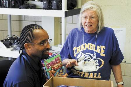 """Long-time volunteer and ardent Chamblee football Bulldogs fan Barbara Moore, right, gives Perry Moss some bone-shaped """"Scooby-Doo cookies"""" to deliver to the football players."""