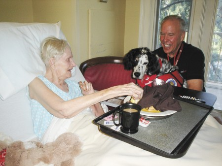 Canterbury Court resident Jackie Lynn enjoys her breakfast in the company of Ranger and his handler, Dave Frew.