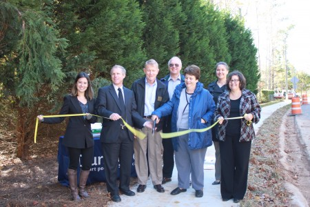 Left to right, Misha Cohen, City Councilman Doug Thompson, City Councilman Denny Shortal, James Edgar, Paula Edgar, Dunwoody Capitol Projects Manager Mindy Sanders and City Councilwoman Lynn Deutsch cut a ribbon to mark the completion of the construction by the city of five miles of sidewalk.