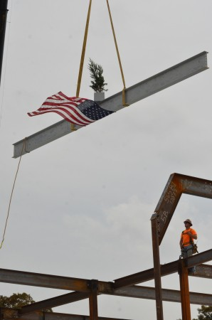 A worker stands by as a special steel beam is lowered into place Oct. 31 during construction of Pace's new Upper School building.