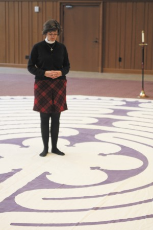 The Rev. Beth Knowlton pauses at the center of the labyrinth inside a building the Cathedral of St. Philip.