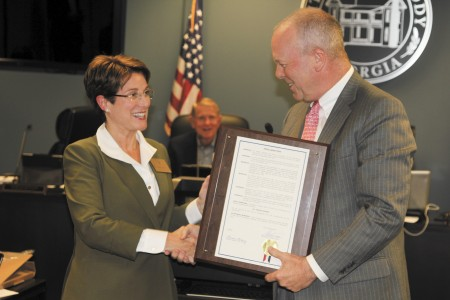 Caption: City Councilwoman Adrian Bonser, left, receives a resolution from Mayor Mike Davis.