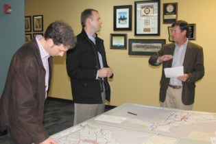 John Wilkes, left, examines a map showing possible new bike path locations while Sandy Springs City Councilman Ken Dishman, center, and Chad Plumly talk at Sandy Springs City Hall.