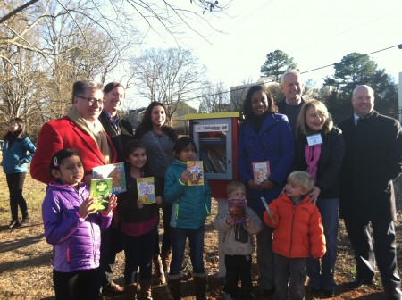 """Officials from the Cross Keys Foundation, the Atlanta Braves Foundation, and the city of Brookhaven gather with children at Briarwood Park to celebrate the new """"free little library."""""""