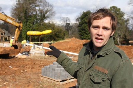 Phil Proctor discusses his design for 'Spiderwalk,' a 'playable' sculpture being installed at the Abernathy Linear Greenway Park in Sandy Springs. Construction crews work on the ground around the yellow body and head of the giant metal spider sculpture. Later, Proctor would add the spider's legs. Photo by Joe Earle on 1/15/2014.