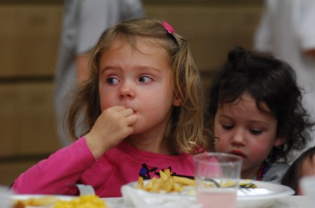 Riley Gilmore, 4, at left, and her friend Audrey Ambler, 5, enjoy dinner March 14 at the Friday night fish fry hosted by the  Knights of Columbus in the gym of All Saints Catholic Church in Dunwoody. Both girls attend pre-school at All Saints.