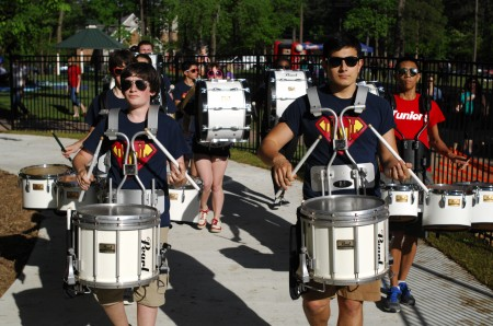 Josh Palgon, left, and Lance Kennedy lead the Dunwoody High School marching band as its marches through Brook Run Park on May 1 during the first Dunwoody Food Truck Thursday of the summer.