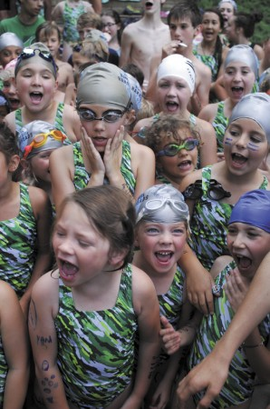 """""""Hammerheads"""" teammates and twin sisters, May Weis, left, and Leah, center, get themselves pumped up before a swim meet against the Byrnwyck """"Blue Dolphins"""" at the Hammond Hills pool on June 3."""