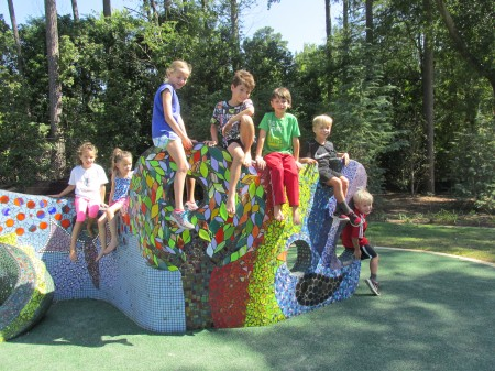 From left, friends Kailee Chronopoulos, Keira Sellers, Marilyn Abney, Andrew Chronopoulos, Finn Sellers, Sydney Abney and Sam Abney enjoy one of the sculptures at the newly opened Abernathy Greenway.