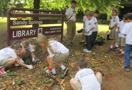 Mount Vernon Presbyterian third-graders help plant flowers in front of the Sandy Springs Library sign.