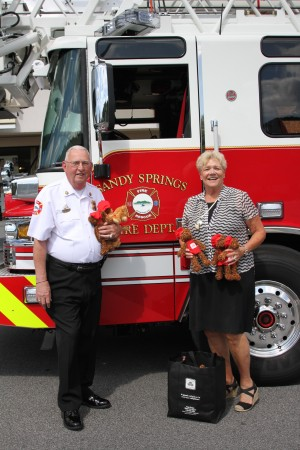 "Sandy Springs Fire Chief Jack McElfish accepts 100 ""Good Neighbears"" from local State Farm insurance agent Fran Farias outside her office on Abernathy Square Tuesday afternoon. Photo by Isadora Pennington"