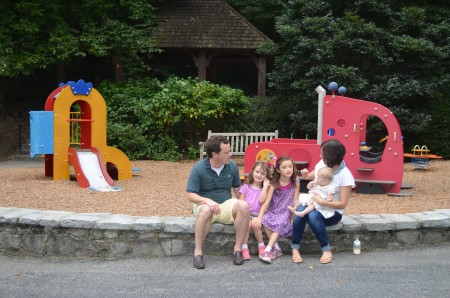 Left to right, Neale Fisher, with daughters Caroline, 5, Virginia, 7, Janie, 10 months, and wife Robin, relax at the Brookwood Hills Community Club's playground.