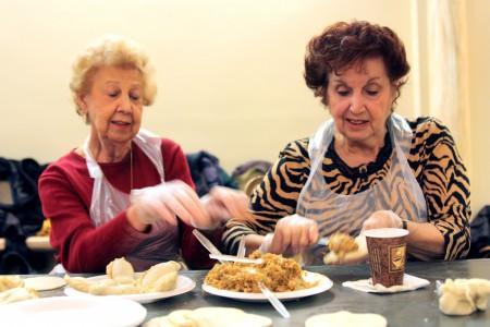 Grace Benator, left, and Renee Feldman make burekas.