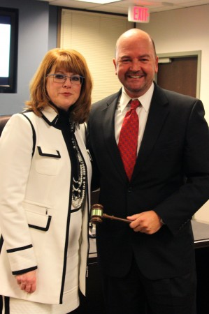 Outgoing Chair of the Dunwoody Chamber of Commerce Board of Directors Paula Owens passes the gavel to incoming Board of Directors Chair Brent Morris during the annual meeting Nov. 18.