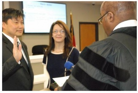 Chief Judge Gregory Adams reads the oath of office to John Park with Park's wife Morgan Harris looking on. Photo courtesy city of Brookhaven