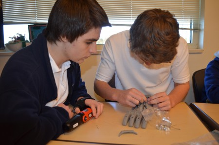 Mount Vernon Presbyterian students Akim Abdiyer, left, and Carson Barber work on a mechanical hand the students are building as part of a class project.