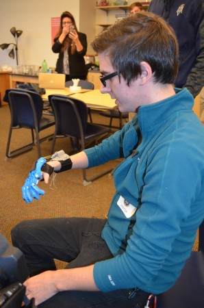 Alex Linkous tries out one of the prosthetic  hands students at Mount Vernon Presbyterian School are making for him using the school's new 3-D printer.