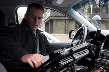 Dunwoody Police Officer Tim Fecht uses a thermal printer inside his vehicle.