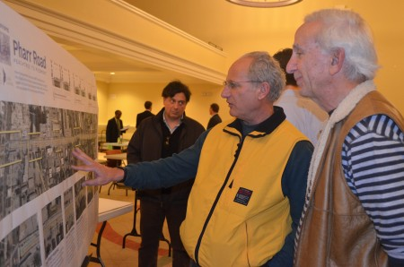 Bruce Salzinger, center, and Steve Jacobs, right, examine plans for painting new lanes on Pharr Road to add bike lanes in the Buckhead village while resident Luke Delporte, left, considers the proposed changes.