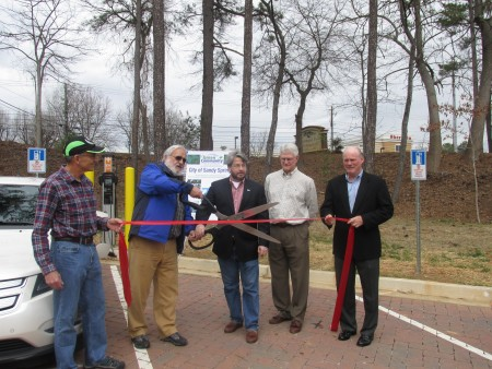 Sandy Springs Councilman Tibby DeJulio cuts the ribbon for the car charging stations as resident Dan Ellithorp (left), Councilman Gabriel Sterling, Parks and Recreation Director Ronnie Young and Douglas Serillo of Charge Point, which installed the stations, look on.