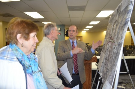 Ellyn Musser, left, and Don Houze, center, discuss the roundabout plan with project manager Ryan Trick of Jacobs.