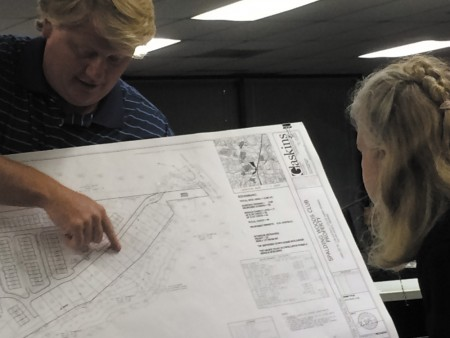 Clif Poston, with Traton Homes, shows resident Lorraine Glynn the updated design for the 99 townhomes proposed for development.