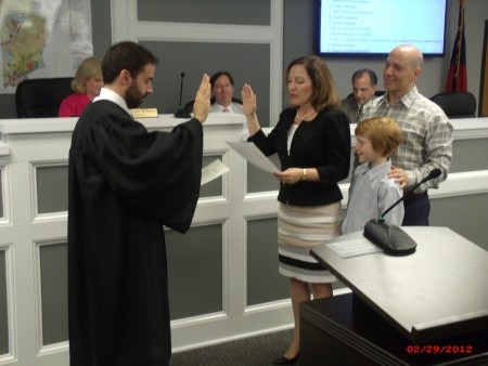 Attorney Linley Jones (center) takes the oath of office for city council, District 1. State Court Judge Mike Jacobs (left) administers the oath, while Jones' husband, Greg and son Elijah Roth look on.