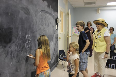 From left, Beck Ballowe draws a clue on a chalkboard as her sister, Evie, brother James, volunteer Suzy Williamson, mom Meggan Ballowe, back left, and Candace Johnson, Sandy Springs United Methodist Church's minister to children and leisure activities, back right, look on.