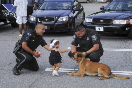 """Perimeter Mall Parking Lot; Tuesday August 4, 2015 6:00pm. Police Night Out event, where police departments from Brookhaven, Chamblee, Dunwoody, and Sandy Springs welcomed the community to look at vehicles, and pick up information regarding public safety. (ltor) Sandy Springs Police Officer D. G. Romero, and his daughter Gianna, 1, petting """"Dak"""" a Belgian Malinois DeKalb County Police Department K-9, and his handler DeKalb County Detective Ronnie Viar."""