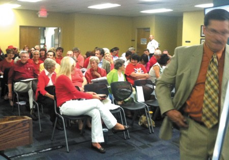 Ashton Woods opponents, wearing red as a symbolic protest to the city's plans, crowd the meeting.