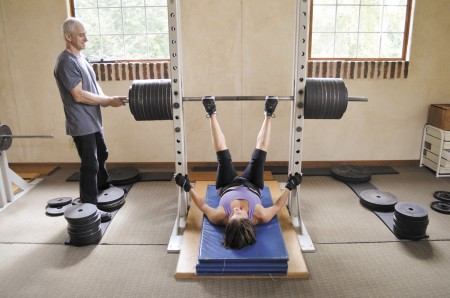 """Client Beth Nowak works out in the gym on Cliftwood Drive in Sandy Springs. Trainer Vladimir Chubinsky brought """"gravitational wellness"""" to the U.S. in 1997, and under his supervision, clients lift weights weighing hundreds of pounds."""