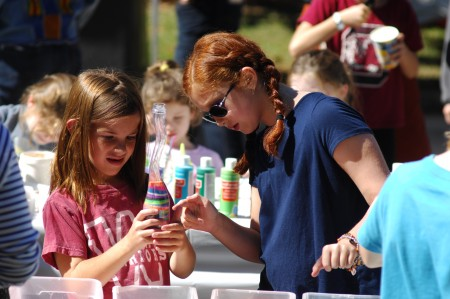 """Apple Valley Road, next to Brookhaven MARTA Rail Station; Brookhaven Arts Festival; Saturday October 17, 2015 1:00pm. Making """"Sand Art"""" Ella Kate McCord (8yr), and Jules schmidt (10yr) [glasses]."""