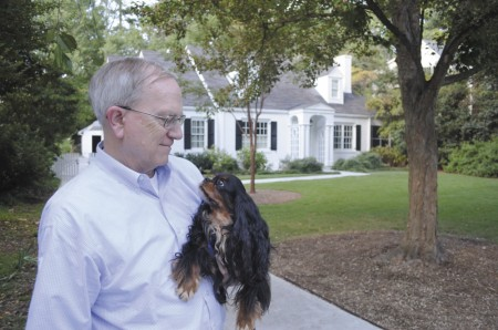 John Matthews takes his dog, Correen, for a stroll in front of the home he's lived in for 42 years.