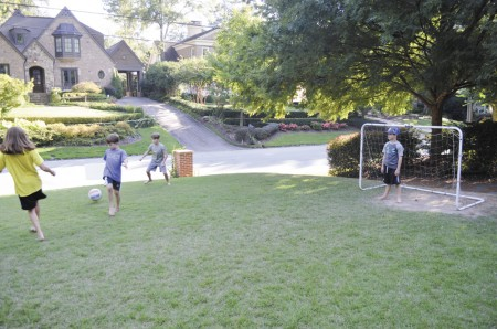 The Taylor boys -- twins Lane and Grant, 7, and Clark, 9, get in a little front yard soccer practice with neighbor Zoe Schroeder.