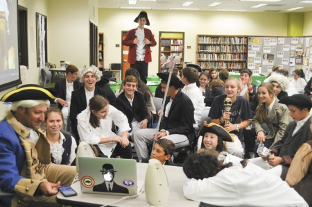 Students re-enacting the Second Continental Congress gather around teacher Matthew Barry's laptop to videochat with a class in Chicago.