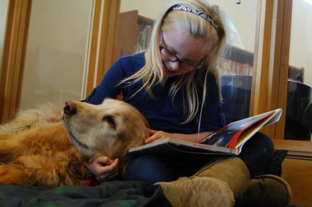 The Happy Trails/READing Paws program at the Buckhead Branch Library gives children the chance to improve their public speaking and reading skills by reading aloud to a therapy dog. Above, Avery Radics, 7, reads to dog Sedona at the Nov. 14 READing Paws event. (Photo by Phil Mosier)
