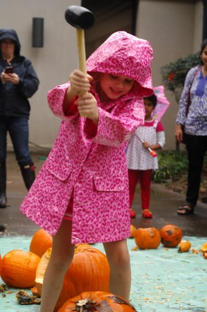 Mary Thatcher, 5, gives a rubber mallet a swing at a pumpkin. (Photo by Phil Mosier)