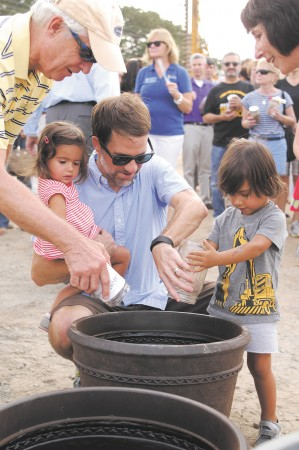 """Mel Mobley, Vann McNeill, center, and his children Seema, 1, and Ravi, 2, right, pour their neighborhood's soil into a planter at the request of Sandy Springs Mayor Rusty Paul, at a ceremony to unveil """"City Springs"""" on Sept. 20."""