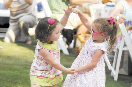 """Ruthie Williams, 3, left, and her friend Anna Harding, 3, dance to the music of """"The Return,"""" a Beatles tribute band performing at Heritage Green in Sandy Springs on Aug. 2. The show was part of the annual Concert by the Springs series."""