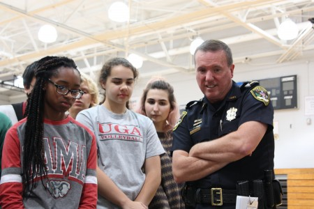 Police Chief Billy Grogan (right) shows students a video about the dangers of distracted driving during a Dec. 3 Town Hall at Dunwoody High School.