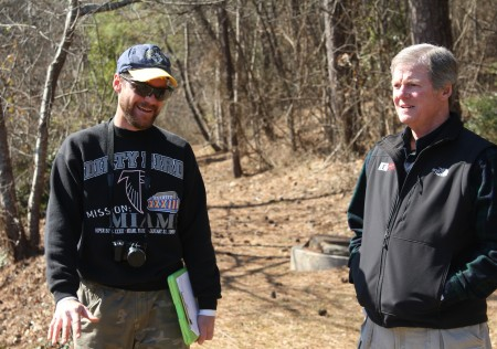 Bobby Sauer Jr. of the state Safe Dams Program, left, explains a point to homeowners association representative Donald Dutson Jr. atop the Powers Lake Dam on Feb. 11. (Photo John Ruch)