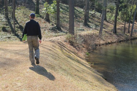 Safe Dams Program inspector Bobby Sauer Jr. walks the top of Powers Lake Dam in Sandy Springs Feb. 11. (Photo John Ruch)