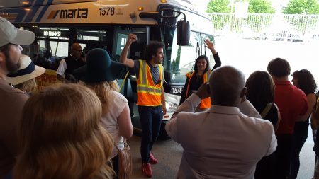 """MARTA Army founder Simon Berrebi (center) pumps up a group about to board a bus at Doraville Station for the April 27 """"bus crawl."""" (Photo John Ruch)"""