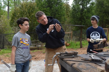 Blacksmith Andrew Crawford examines the twist in a metal bar while student Oliver Schouest, at left, looks on.