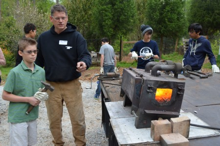 Blacksmith Andrew Crawford and his son, Edward, by Crawford's portable forge.